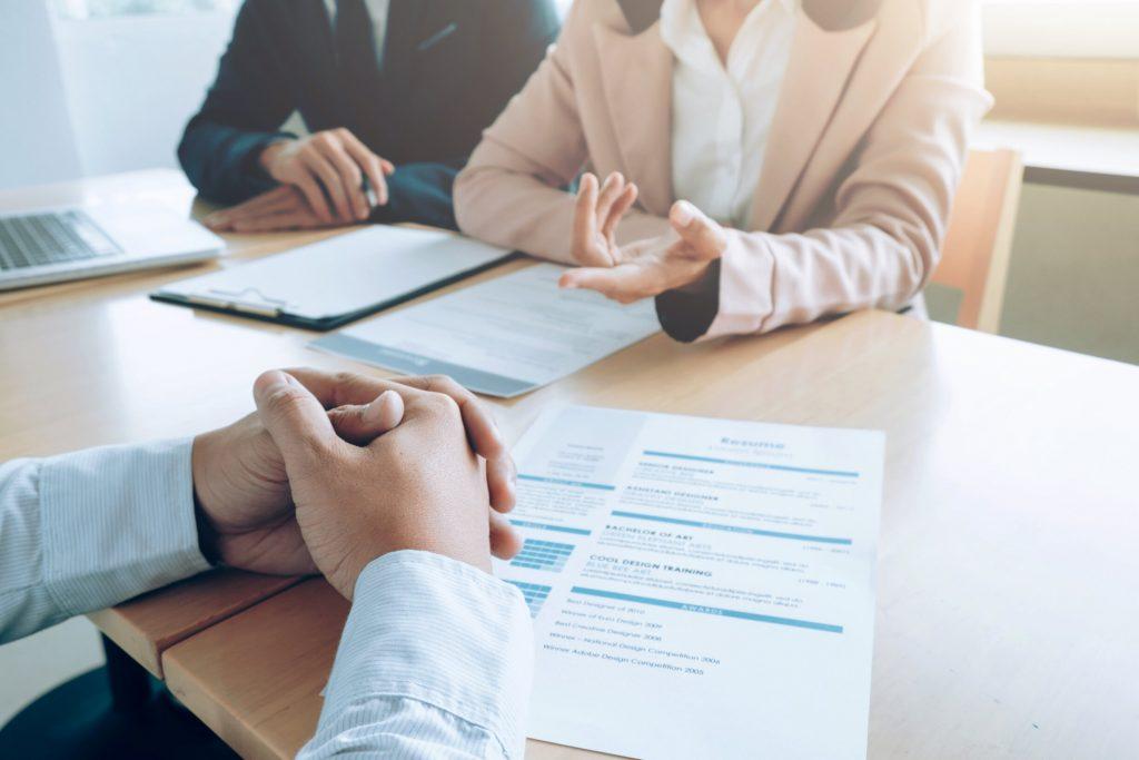 Foto dua komite ketenagakerjaan sedang mewawancarai calon pegawai dan menilai kemampuan hard-skill serta komunikasi.